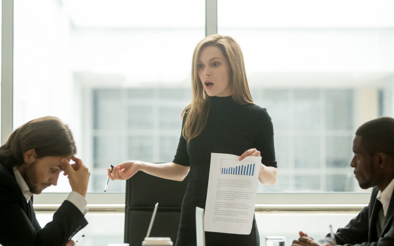Dissatisfied angry female executive scolding her team