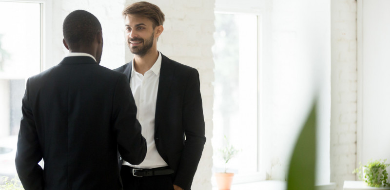 Diverse successful businessmen standing talking in office