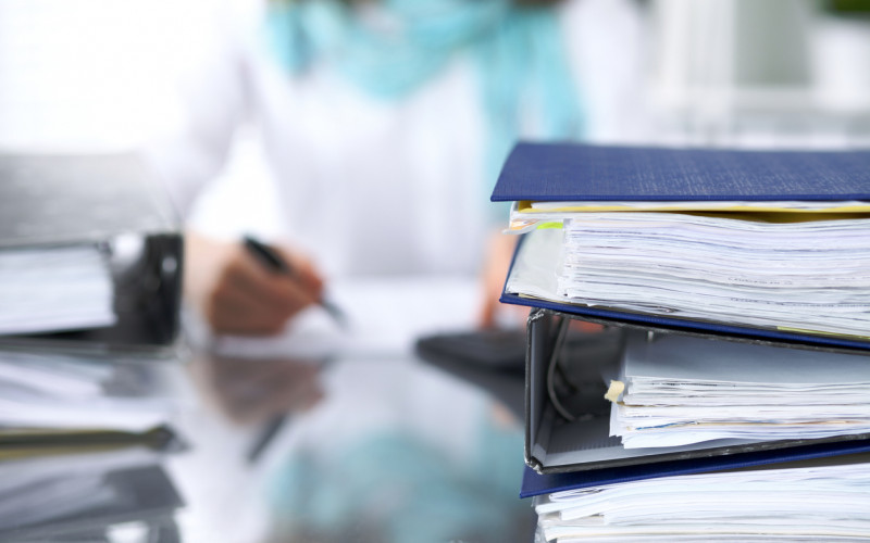 Large stack of binders with papers and a business person back in blur.