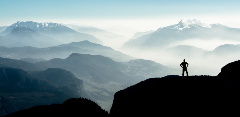 Beautiful view snow covered mountain ranges silhouettes and fog filled valleys with bright back light. South Tyrol, Itay, Alps. Happy winning success man at sunset or sunrise standing relaxed and is happy for having reached mountain top .