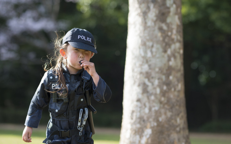 Little girl blowing a police whistle