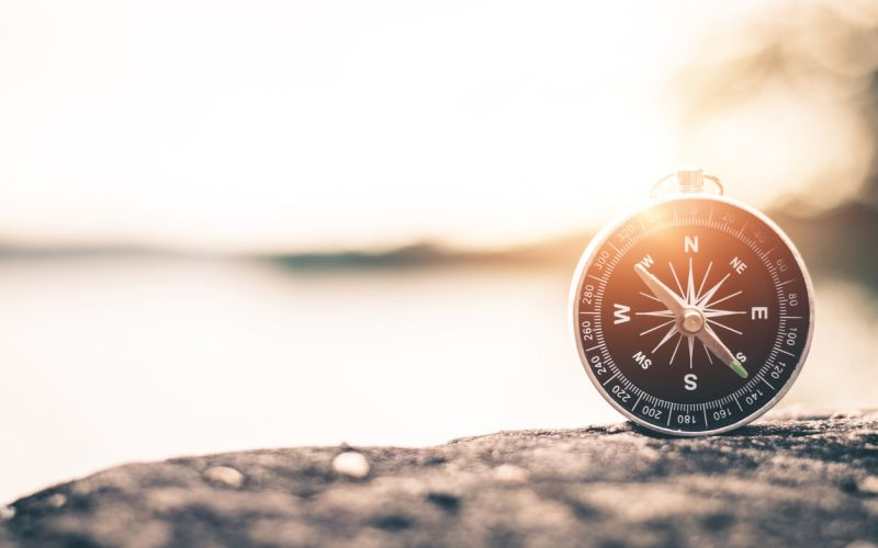 Compass with mountain at sunset sky background.