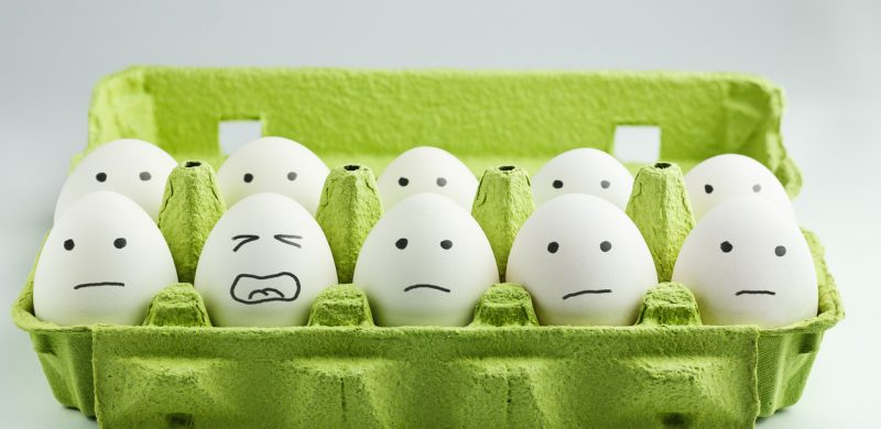 egg carton w/ unhappy faces drawn on the eggs.
