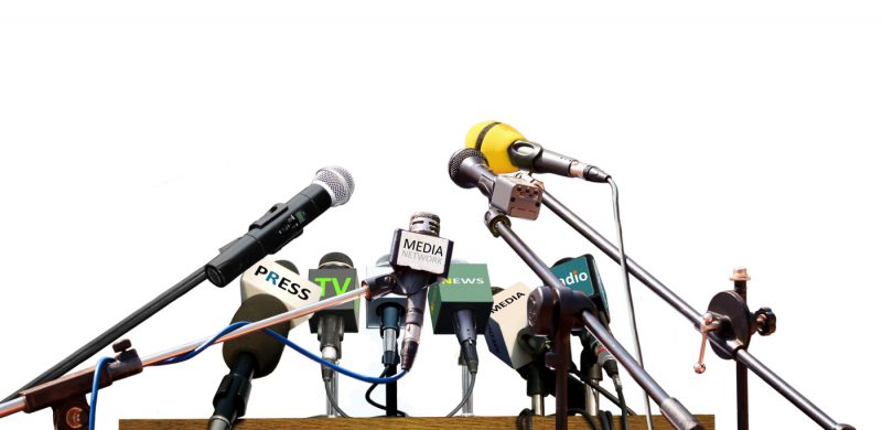 Press conference microphones standing on white background