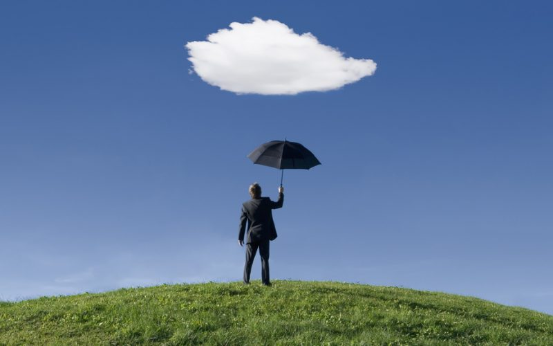 Businessman on a hill holding umbrella underneath a single cloud themes of protection shelter out of context