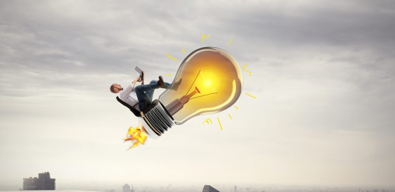 Man sitting on light bulb rocket while working on a laptop