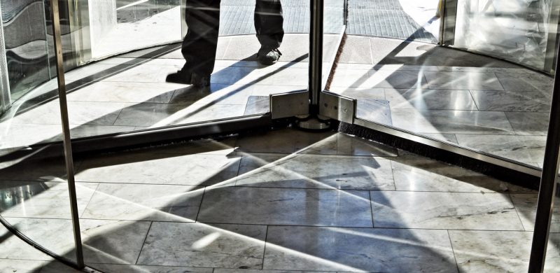 Feet of a man walking in revolving door