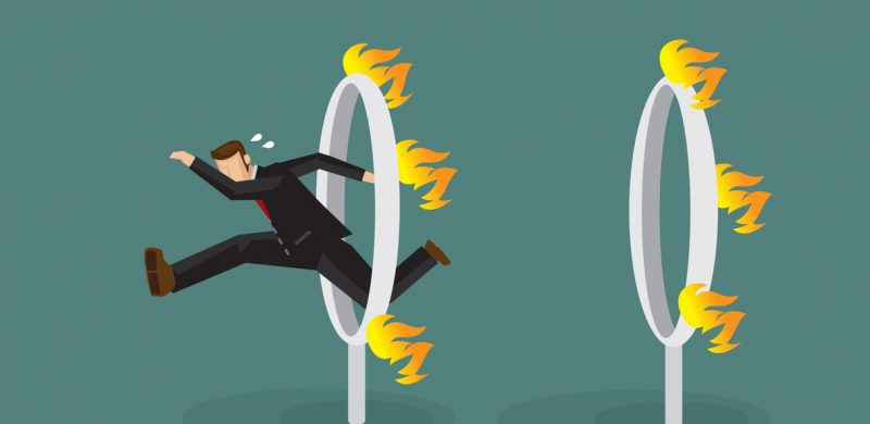 business man jumping through fire hoops
